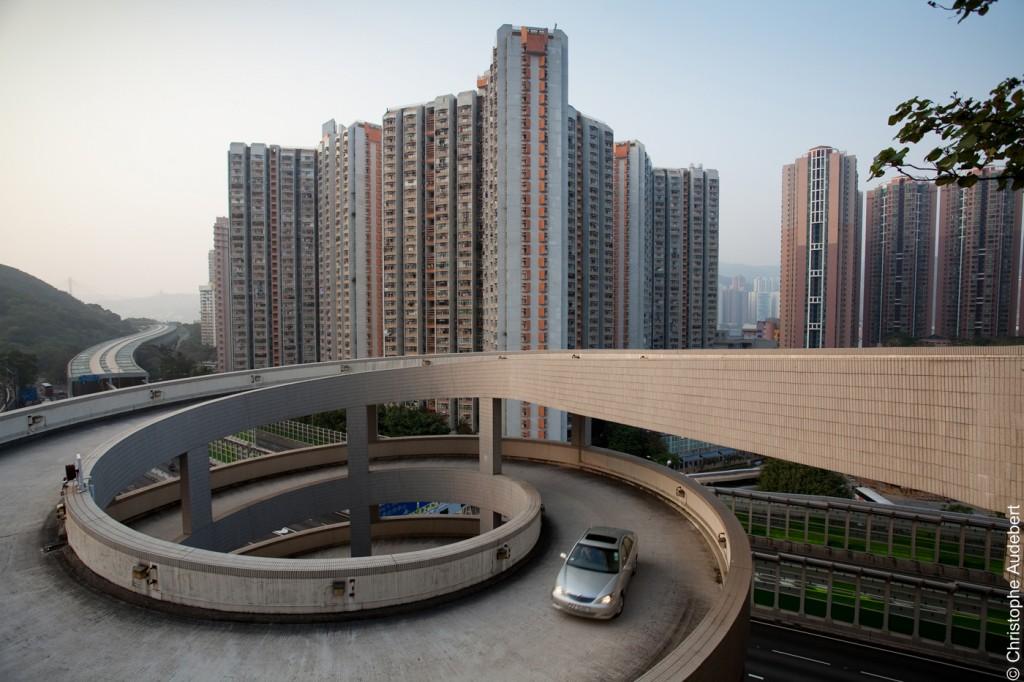 Voiture sortant d'un parking à Hong Kong avec en arrière plan des tours d'habitation dépassant les 50 étages.