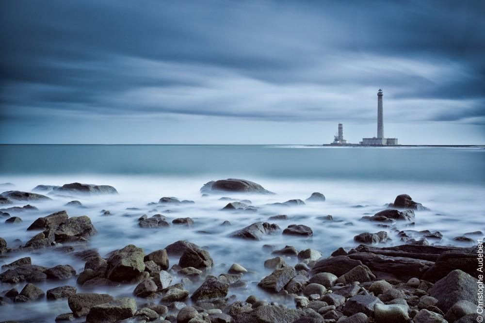 Grand phare de Gatteville sous un ciel nuageux avec bord de mer et rochers en premier plan. Prise de vue en pose longue dans le Cotentin en Normandie, France. Noir et blanc.
