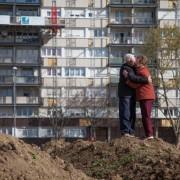 Couple d'amoureux agé s'embrassant dans un décor urbain debout sur un tas de terre devant une barre d'immeubles à Asnières-sur-Seine (92)