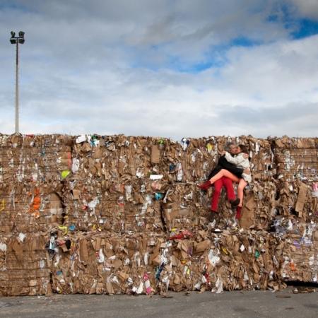 Couple d'amoureux s'embrassant dans un décor industriel assis sur un tas de papiers à recycler, Genevilliers (92)