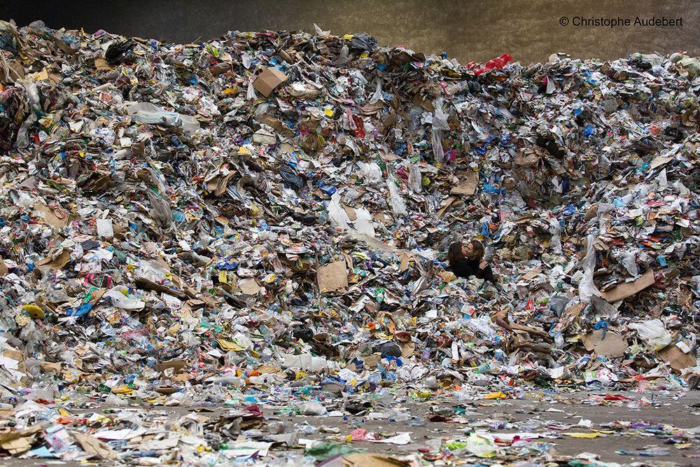 Couple d'amoureux dans un tas de papiers à recycler