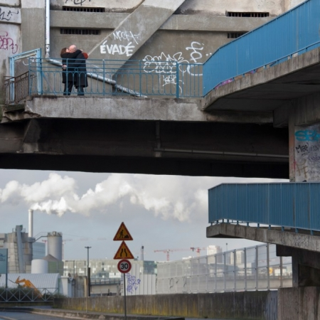 Couple d'amoureux s'embrassant dans un décor urbain pollué et plein de graffitis. Passerelle bleue et fumées d'usine.. Ivry-sur-Seine (92)