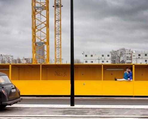 Couple d'amoureux s'embrassant dans un décor urbain: grues, palissage jaune, taxi anglais, à Pantin (93)