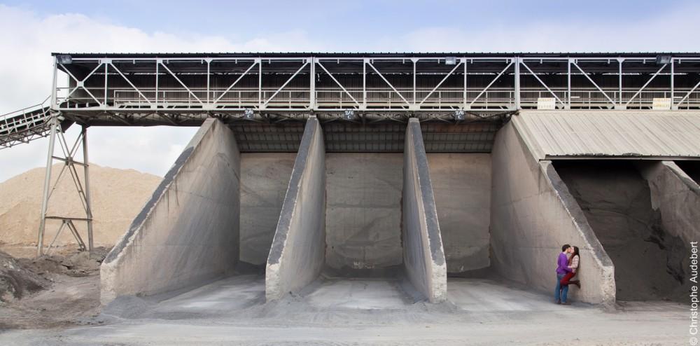 Couple d'amoureux s'embrassant dans un décor industriel debout dans des silos vides à Gennevilliers (92)
