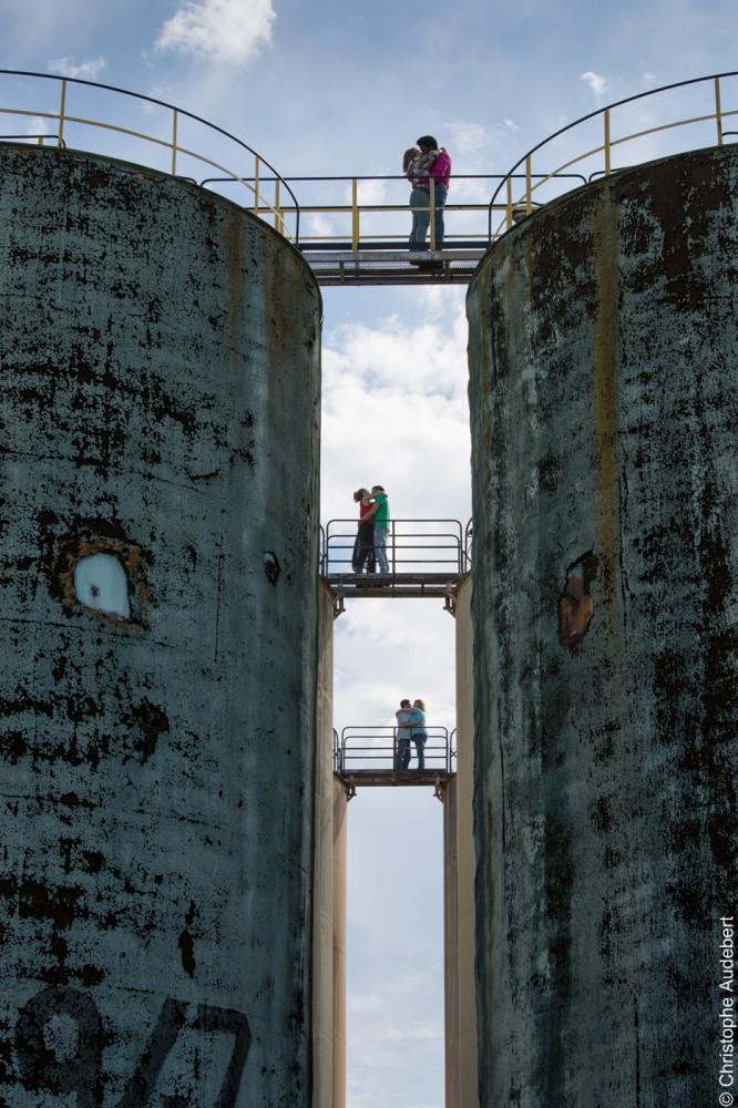 Trois couples d'amoureux s'embrassant sur une passerelle au dessus de deux réservoirs dans une raffinerie à Nanterre (92)