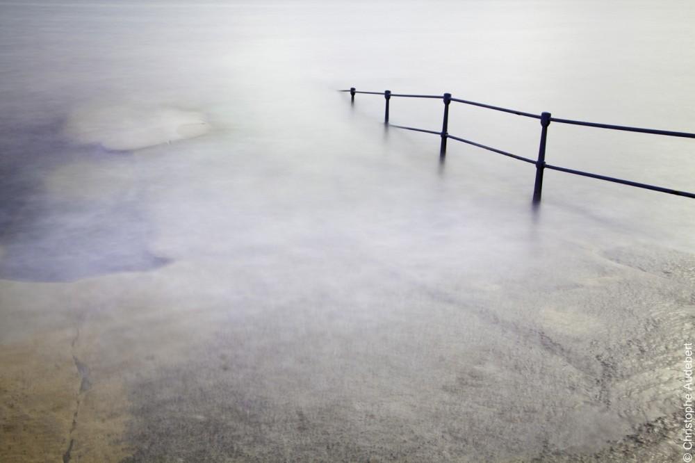 piscine d'eau de mer remplie avec la marée laissant apparaitre la rambarde de protection. Prise de vue en pose longue à Guernesey, Royaume Uni.