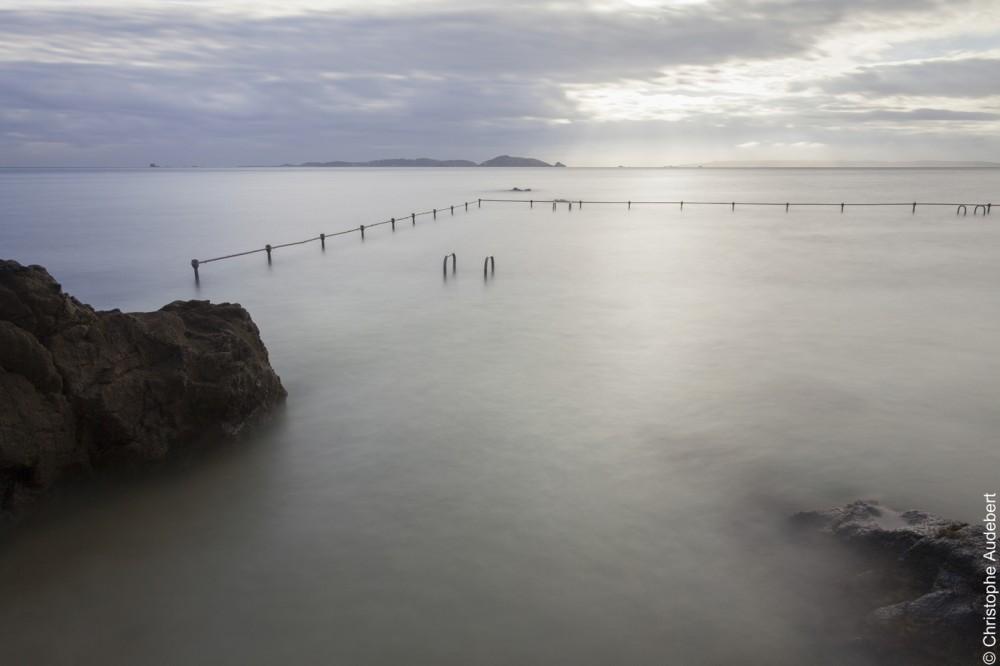 piscine d'eau de mer remplie avec la marée laissant apparaitre à moitié deux échelles et la rambarde de protection. Prise de vue en pose longue à Guernesey, Royaume Uni.