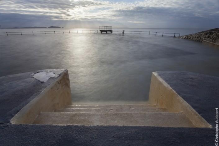 Marches descendant dans une piscine d'eau de mer avec vue sur un plongeoir, à Guernesey, Royaume Uni. Prise de vue en pose longue.