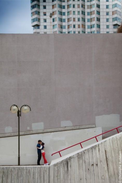Baiser de couple dans un décor urbain devant un grand mur gris à Beaugrenelle, Paris