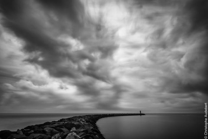Digue de mer à l'embouchure de l'Aude sous un ciel orageux. Prise de vue en pose longue en Méditerranée, France. Noir et blanc.