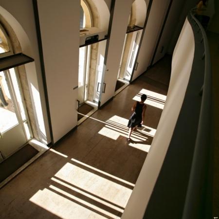 Femme traversant le hall du Pavillon Populaire entre ombres et lumières, à Montpellier, France