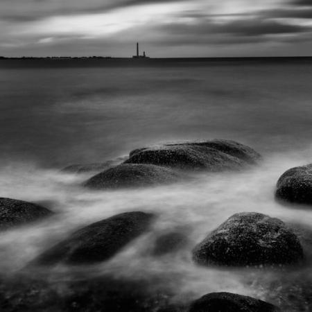 Grand phare de Gatteville dans le lointain avec bord de mer et rochers en premier plan. Prise de vue en pose longue dans le Cotentin en Normandie, France. Noir et blanc.