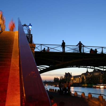 Personnes attendant et marchant sur le Pont des Arts à Paris en bord de Seine au coucher du soleil