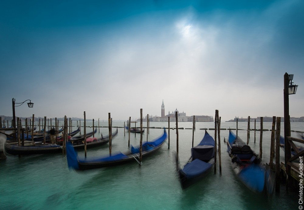 Vue classique de gondoles avec des housses bleues face à la presqu'île de la Giudecca à Venise