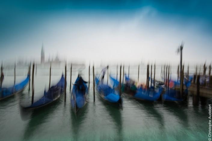 Gondoles bleues et gondolier solitaire face à la Giudecca, Venise, Italie