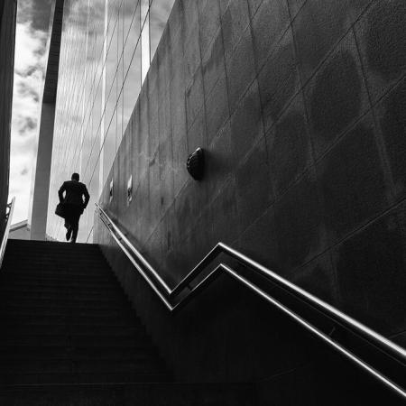 Silhouette d'un homme en costume gravissant un escalier à la défense, Paris