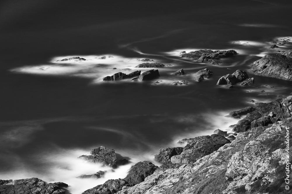 Bord de mer et rochers sur la cote des Cornouailles, Royaume-Uni. Prise de vue en noir et blanc, en pose longue.