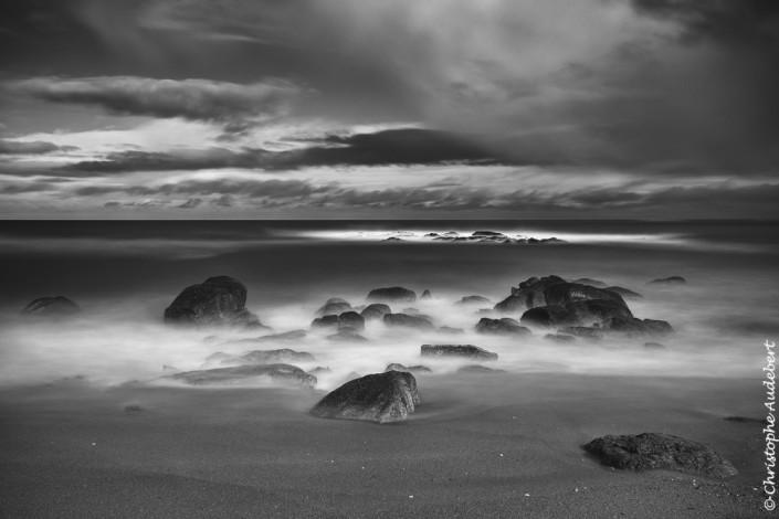 Mers et rochers dans le Cotentin en Normandie. Prise de vue en noir et blanc et en pose longue.