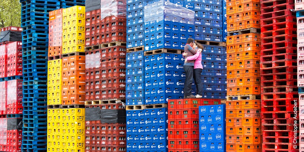 Couple s'embrassant juché sur des containers multicolores