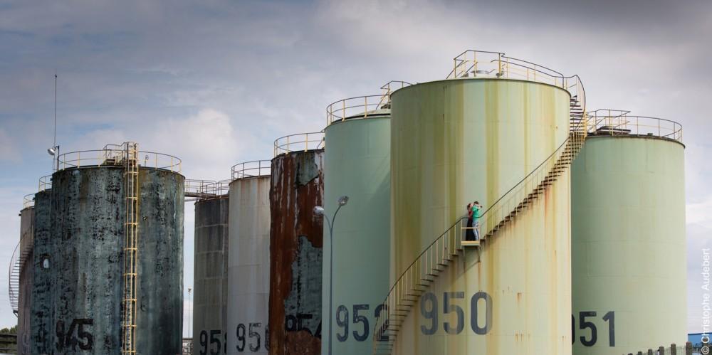 Couple enlacé sur l'escalier d'un réservoir pétrolier