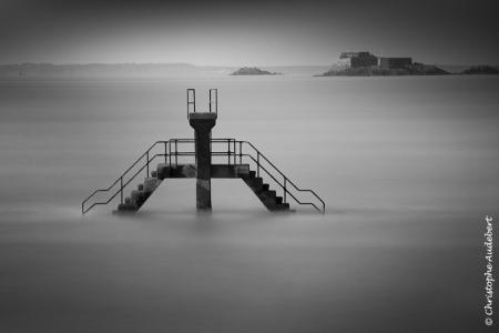 Plongeoir de la piscine d'eau de mer à Saint-Malo en Bretagne. Prise de vue en noir et blanc et en pose longue.