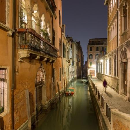 Ombre d'un passant au bord d'un canal la nuit, à Venise, Italie