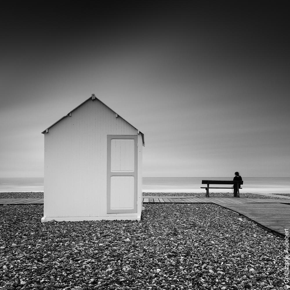 Cabine sur la plage de Cayeux-sur-mer, avec personnage assis sur un banc